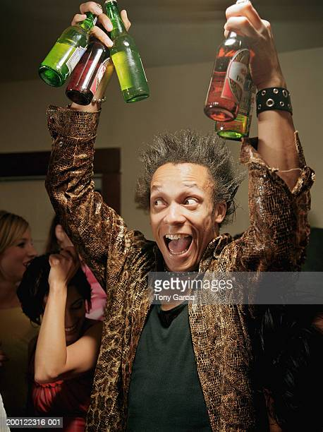 Young man holding up  beer bottles at party