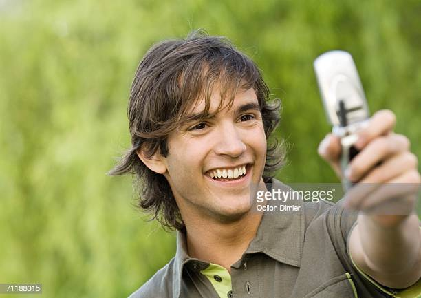 Young man holding up cell phone and smiling