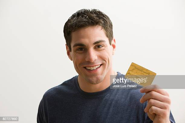 Young man holding up credit card