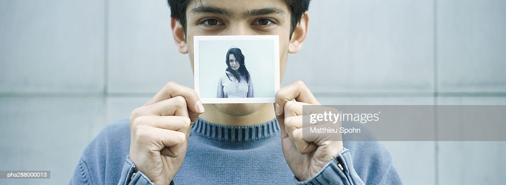 Young man holding up photo of young woman : Stockfoto