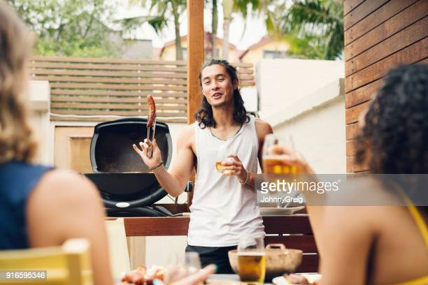 young man holding up sausage in front of barbecue with friends on foreground - funny bbq stock pictures, royalty-free photos & images