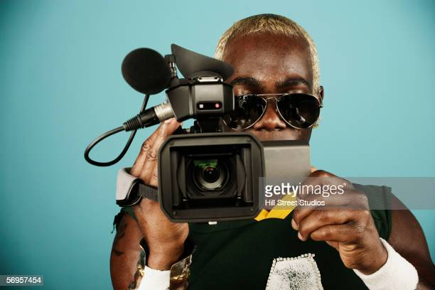 Young man holding video camera