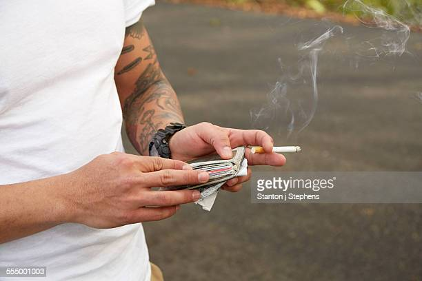 Young man holding wallet and smoking cigarette, mid section