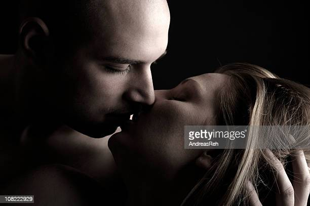 Young Man Holding Woman's Head and Kissing Her, Low Key
