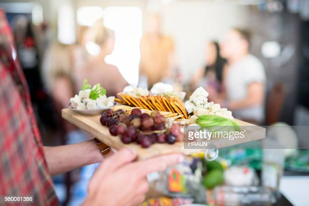 young man holding wooden tray with various food - cracker snack stock photos and pictures