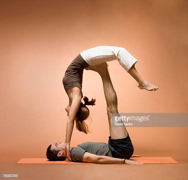 young man holding young woman in yoga pose on outstretched legs - woman straddling man stock pictures, royalty-free photos & images