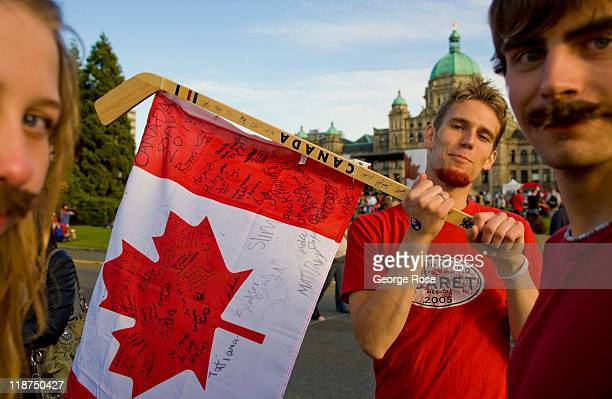 A young man holds a Canadian flag strung on a hockey stick while awaiting the Canada Day inner harbour fireworks show on July 1 2011 in Victoria...