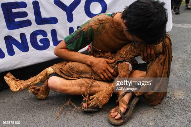 A young man holds a mock flood victim in his arms in Quezon city The Members of the clergy and the Sto Domingo community held a Penitential Walk in...