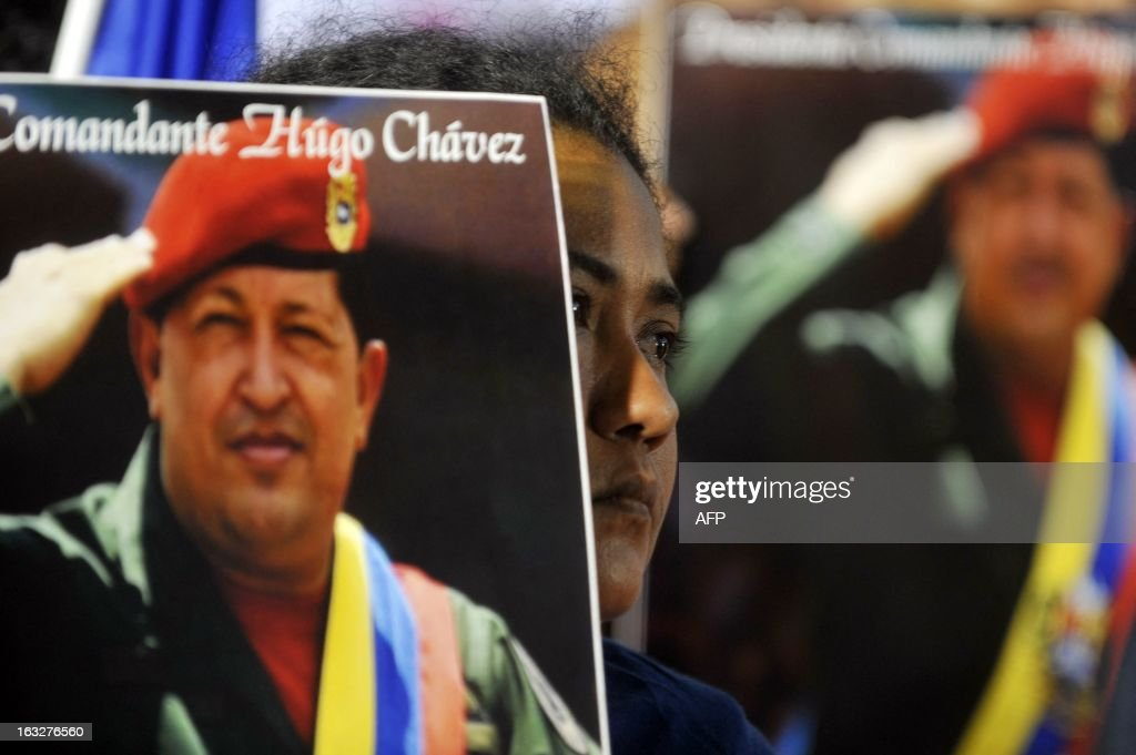 A young man holds a picture of lat venezuelan President Hugo Chavez during an ecumenical service held for him in Managua, on March 6, 2013. The flag-draped coffin of Venezuelan leader Hugo Chavez was borne through throngs of weeping supporters on Wednesday as a nation bade farewell to the firebrand leftist who led them for 14 years. AFP PHOTO/Hector RETAMAL