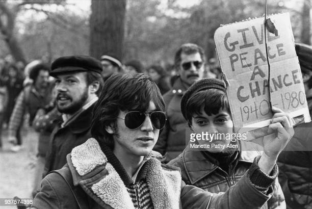 Young man holds a sign saying 'Give Peace a Chance 19401980' as people commemorate John Lennon in Central Park in New York after his death in 1980