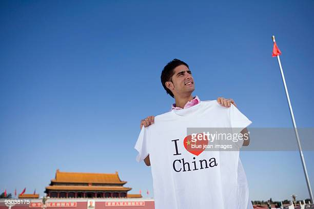Young man holds an I Heart China t-shirt in front of Tiananmen Gate, Beijing, China