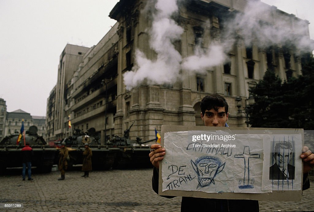 A young man holds up a hand-drawn poster denouncing Romanian president Nicolae Ceausescu in Palace Square, later renamed Revolution Square, Bucharest, during the Romanian Revolution, December 1989.