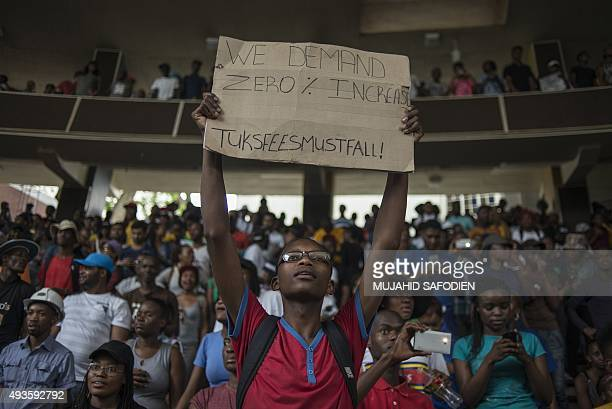 A young man holds up a sign reading '#TuksFeesMustFall' during a demonstration against the increase in university fees at the University of Pretoria...