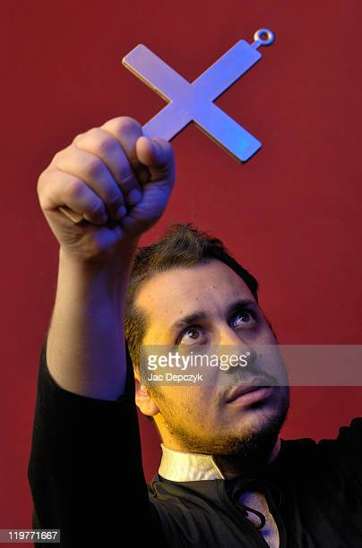young man holds up crucifix, red background. - depczyk stock pictures, royalty-free photos & images