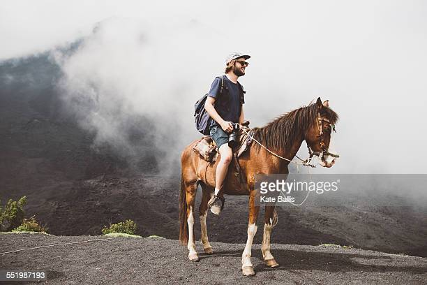 Young man horse trekking at Pacaya volcano, Antigua, Guatemala