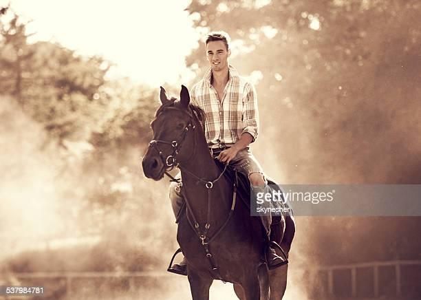 Young man horseback riding.
