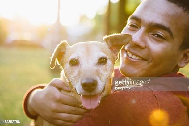 young man hug his small Mixed-breed dog, looking at camera