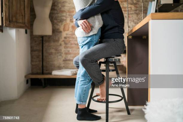 Young man hugging girlfriend from kitchen stool