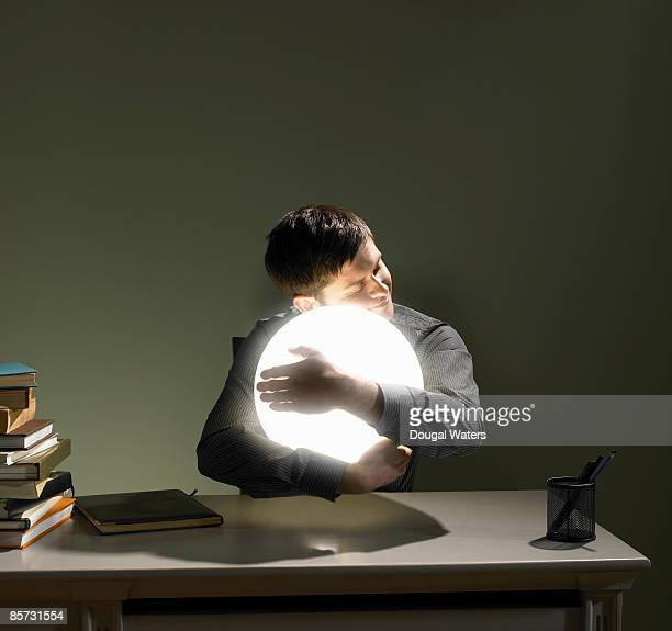 Young man hugging orb of light.