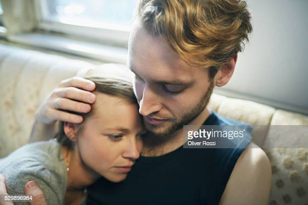 Young man hugging serious woman on couch