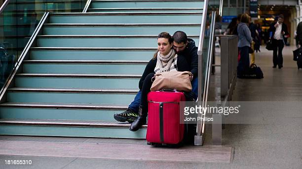 Young man hugs a young woman as the sit with their bags, waiting, on steps at St Pancras Station.