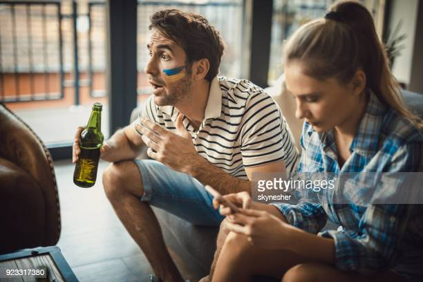 Young man ignoring his girlfriend while watching sports match on TV.