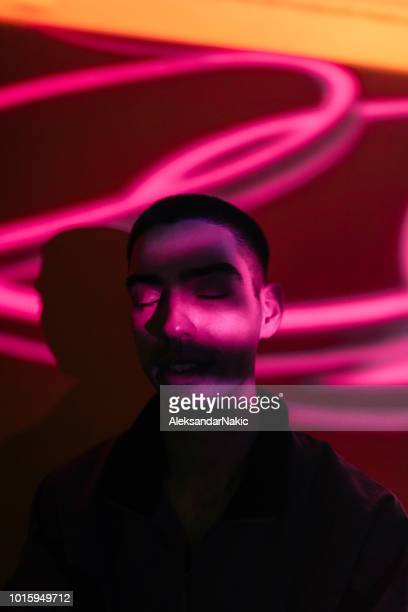 young man illuminated by neon lights - fluorescent light stock pictures, royalty-free photos & images