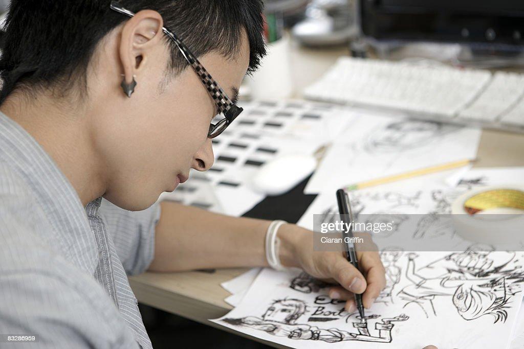 Young man illustrating comics at his desk : Stock Photo