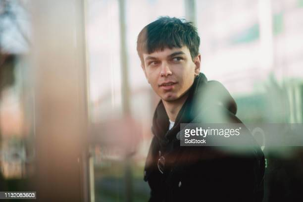 young man in a bus stop - street style stock pictures, royalty-free photos & images