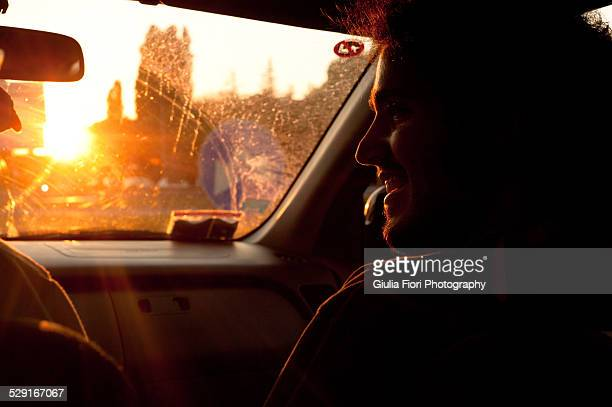Young man in a car at sunset