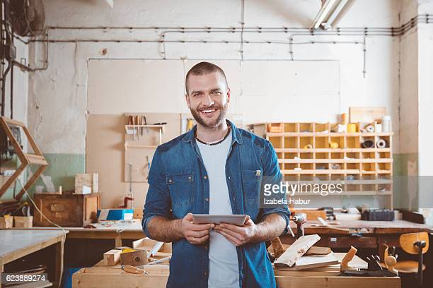 young man in a carpentry workshop - e commerce - fotografias e filmes do acervo