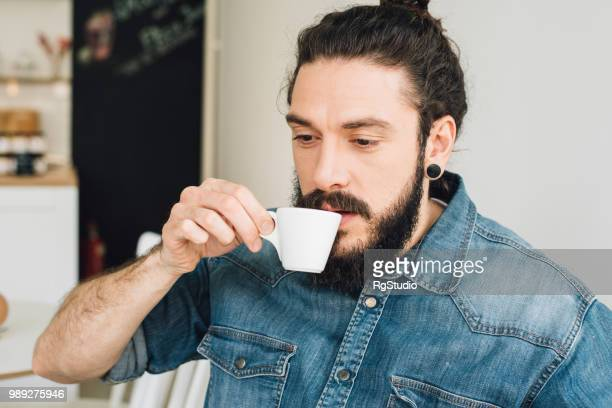 young man in a coffee shop drinking coffee - man bun stock pictures, royalty-free photos & images