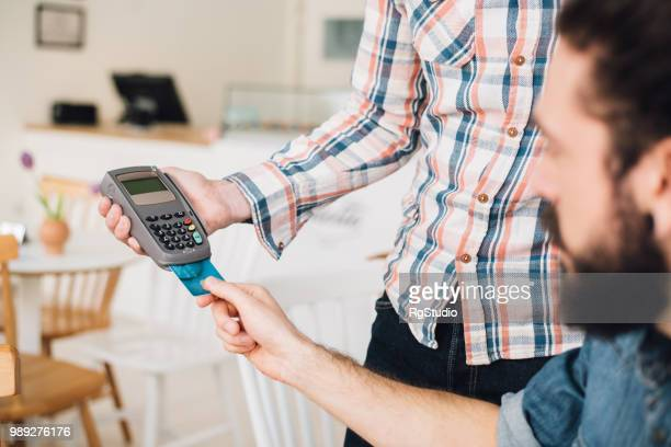 Young man in a coffee shop putting his credit card in a credit card reader