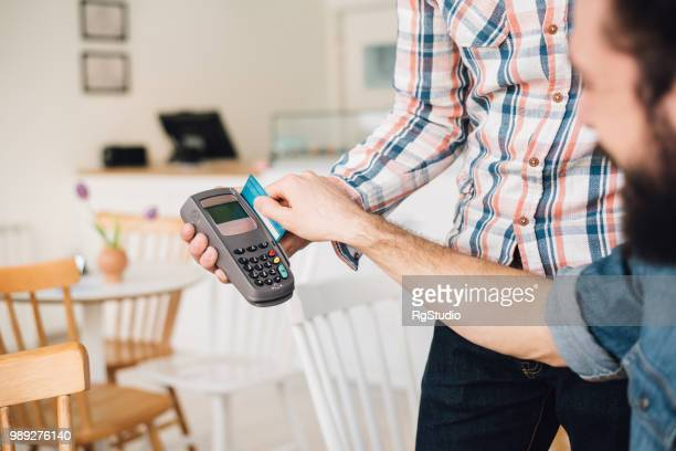 Young man in a coffee shop using his credit card