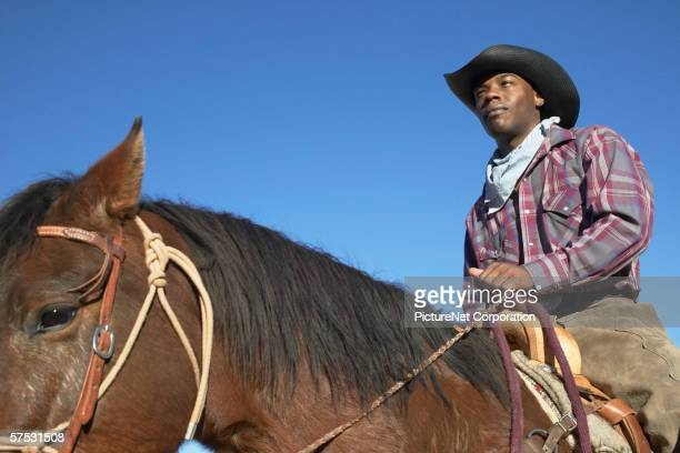 Young man in a cowboy outfit riding a horse
