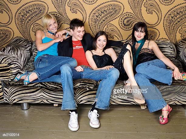 young man in a group of women sitting on a zebra print sofa - quattro persone foto e immagini stock