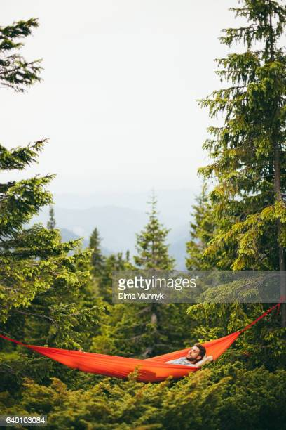 Young man in a hammock in the mountains