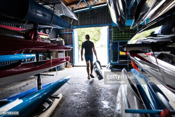 Young man in a kayak and canoe storage room.
