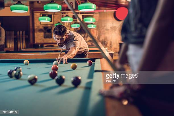 Young man in a pool hall playing billiard.