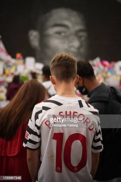 Young man in a Rashford football shirt looks at the messages of support displayed at the newly repaired mural of England footballer Marcus Rashford...