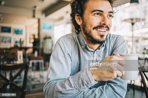Junger Mann in einem restaurant halten Tasse