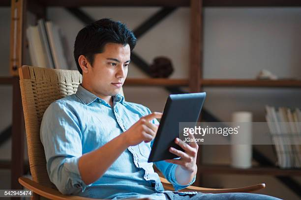 Young man in a rocking chair using digital tablet