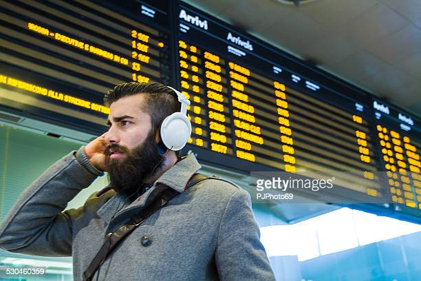 Young man (stylish hipster) in a station or airport
