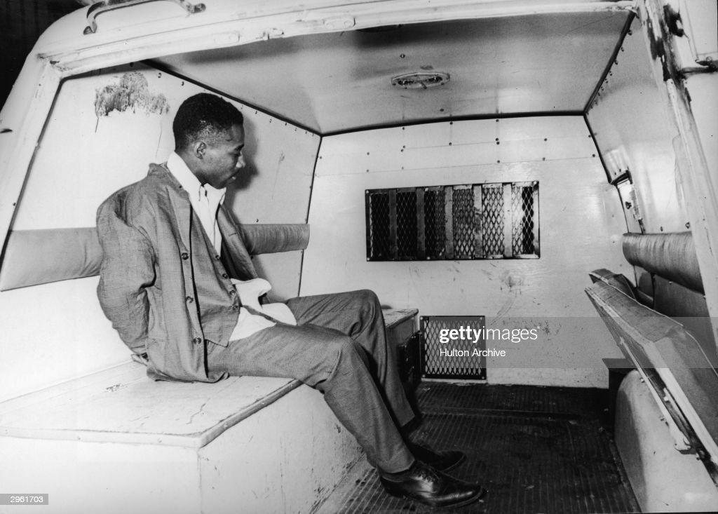 A young man in a suit and waistcoat sits handcuffed in the back of a police wagon during a riot, Newark, New Jersey, July 1967.