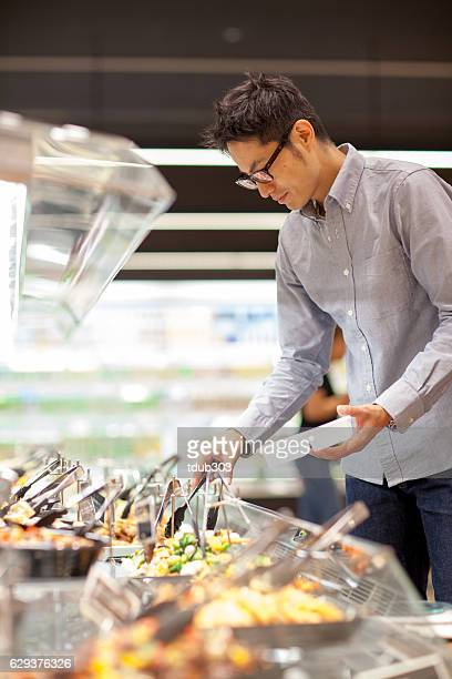 Young man in a supermarket shopping in the deli section
