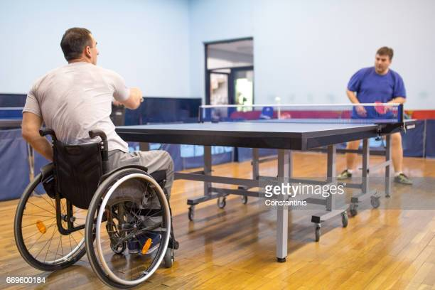 young man in a wheelchair is playing table tennis