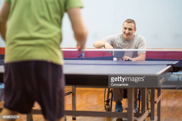 young man in a wheelchair is playing table tennis - assistive technology stock photos and pictures
