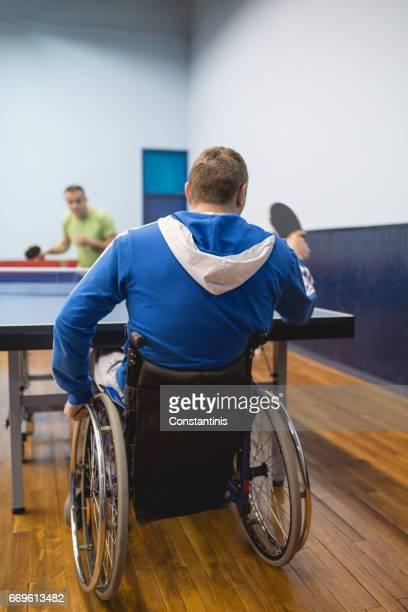 jeune homme en fauteuil roulant est jouer au tennis de table