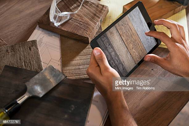 A young man in a workshop which uses recycled and reclaimed lumber to create furniture and objects. Using a digital tablet to keep records and photograph objects.