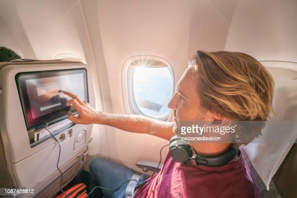 機内エンターテイメントを使用して航空機の若い男 - 乗り物に乗って ストックフォトと画像